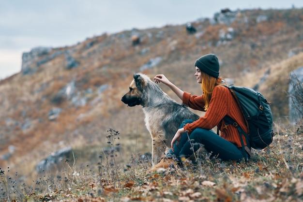 女性は自然の山の友情犬の風景を旅します