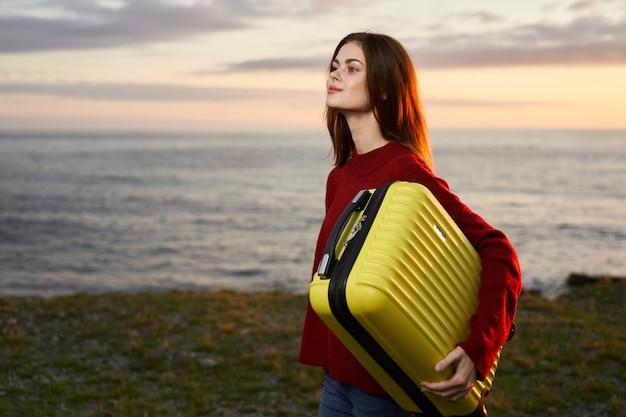 女性は海のスペース、黄色のスーツケースに旅行します