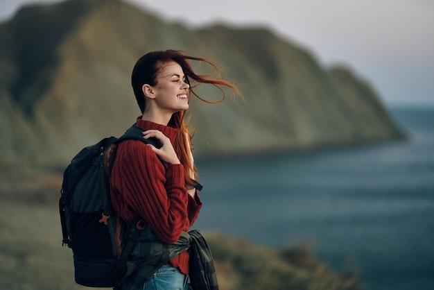 女性はバックパックを持って海の近くの自然の山の中を屋外で旅行します