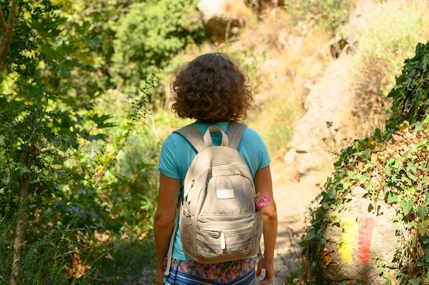 日当たりの良い夏の日に女性がクレタ島の山の峡谷を旅します。
