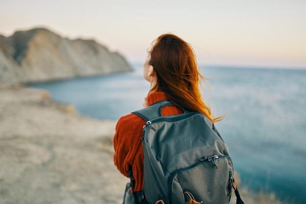 여자는 자연의 산에서 바다 근처 배낭 여행