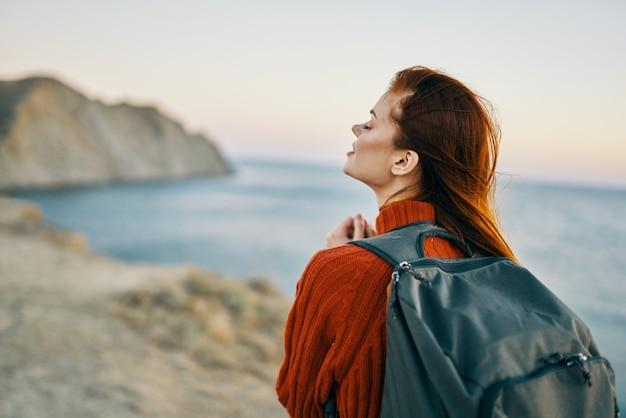 女性は自然の山の海の近くでバックパックを持って旅行します