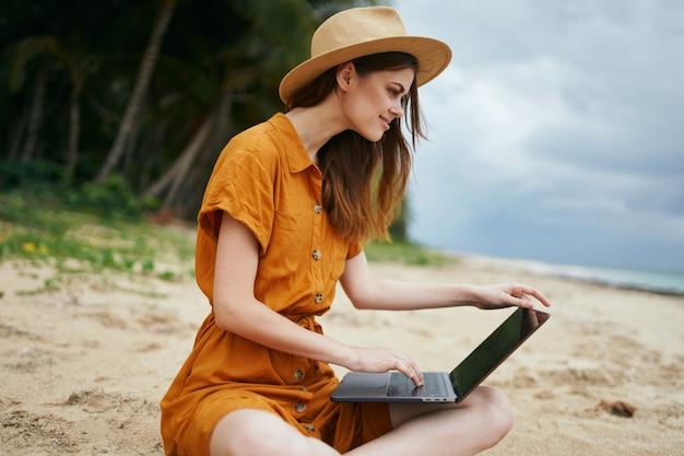 ヤシの木が砂に沿って海に沿ってラップトップで旅行する女性
