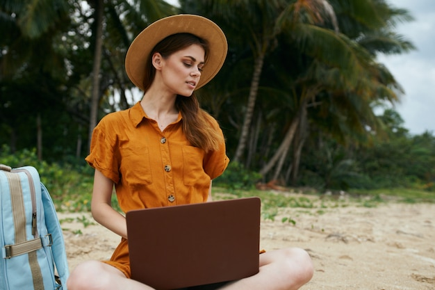 A woman travels with a laptop along the ocean along the sand with palm trees