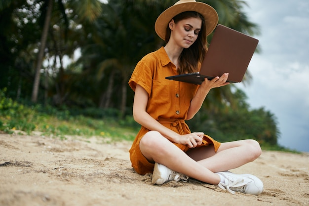 Woman travels with a laptop along the ocean along the sand with palm trees