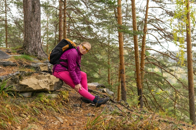 Woman trekker sitting on a mountain trail and holding on to a sore knee