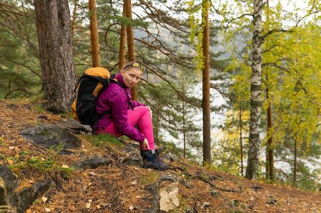 登山道に座ってひざの痛みを抱えてフレームを見ている女性トレッカー