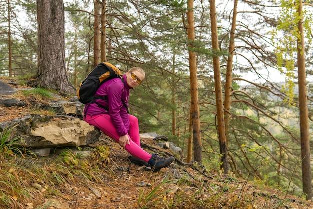 登山道に座ってひざの痛みを抱えている女性トレッカー