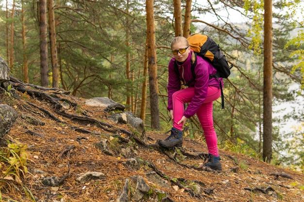 女性トレッカーが登山道に立ち寄り、足首の痛みを抱えてフレームを見ている