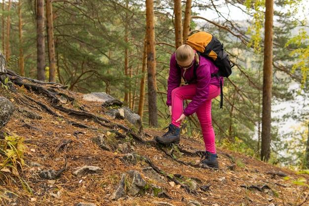 女性トレッカーが登山道に立ち寄り、足首の痛みを抱えていた