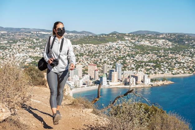 地中海を見下ろす、カルペのペニョンデイファッハの小道に沿ってトレッキングする女性。