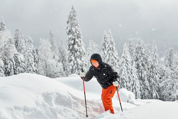 降雪時に冬の峠を通るトレイルをトレッキングする女性