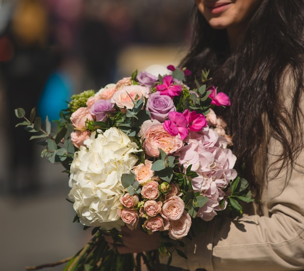 Woman in trench coat holding a mixed bouquet of winter flowers.