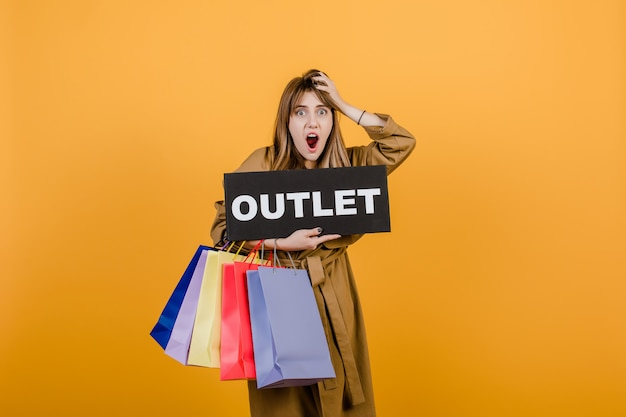 Woman in trench coat with outlet  sign and colorful shopping bags isolated over yellow