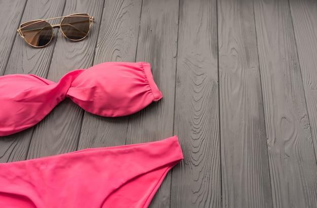 여성 트렌드 투피스 수영복 비치 핑크 수영복 패션 선글라스. 여름 배경