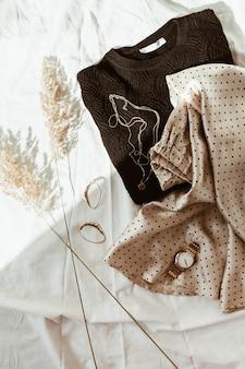 白いリネンのベッドの上の女性の流行のファッションの服。フラットレイ、上面図。黒のセーター、水玉模様のシルクのスカート、ゴールドのネックレス、時計、イヤリング、葦