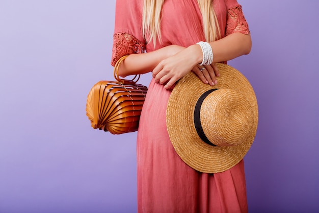 Woman in trendy pink dress and straw hat holding bamboo bag on violet.