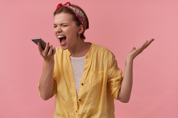 Woman in trendy summer outfit and red bandana with arms gesticulates with smart phone emotion shouting out loud scream mad on gadget isolated on pink