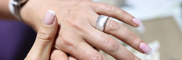 Женщина примеряет широкое серебряное кольцо на палец