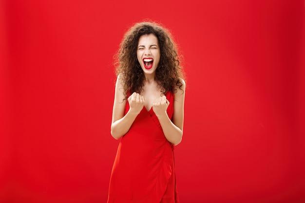 행복과 기쁨 닫기에서 외치는 가슴 근처에서 즐겁게 주먹을 들고 승리하고 환호하는 여자