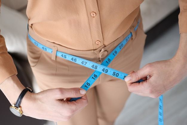 Woman in trousers measuring waist with centimeter tape closeup