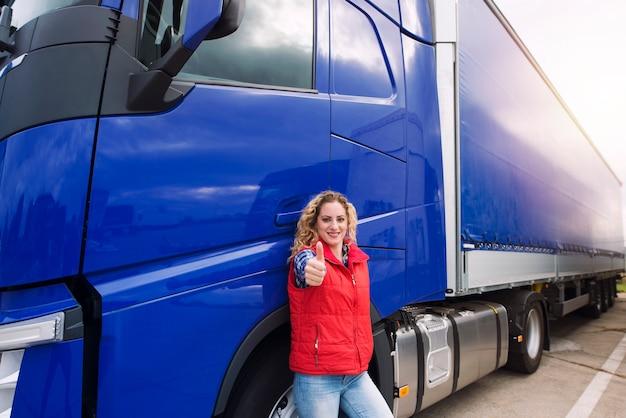 車のドアのそばに立って、トラックの車の前で親指を見せている女性のトラック運転手。