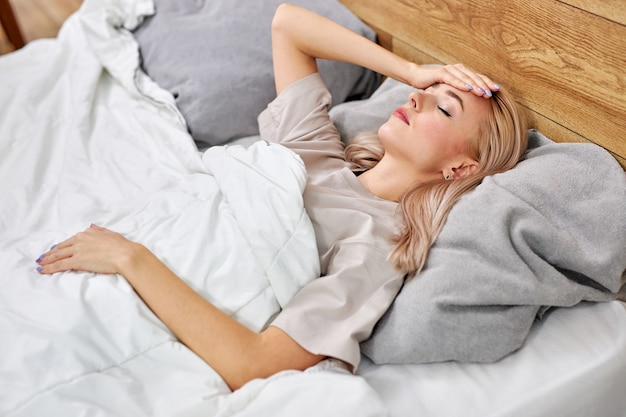 Woman try to bring fever down alone at home. cold symptoms and coauses. sick caucasian woman with flu or coronavirus. female is quarantined, having pain in throat