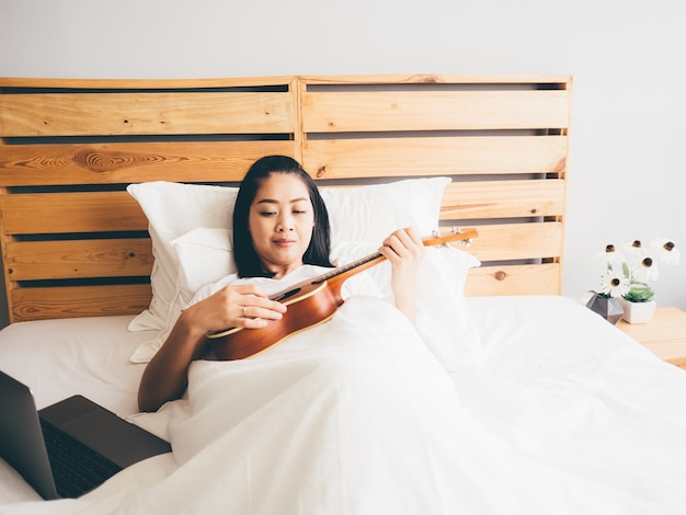 Woman try to learn ukulele in her bedroom.