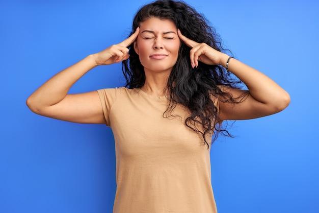 女性は何かを思い出そうとし、目を閉じて立ち、寺院で指を持っています