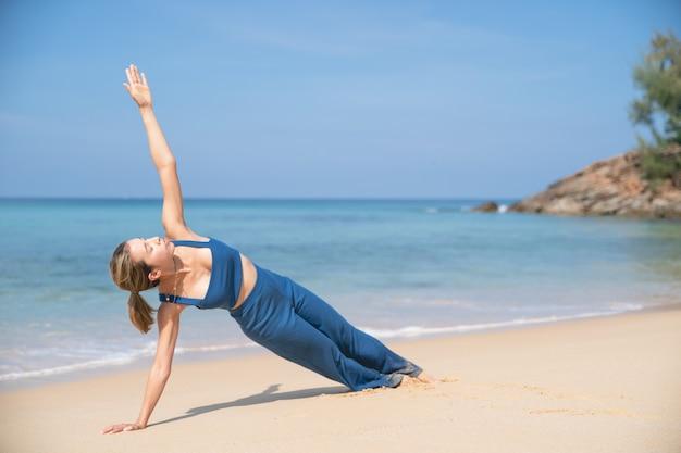 여자는 요가 포즈로 몸을 강화하려고합니다. 해변에서 한쪽 팔에 측면 판자.