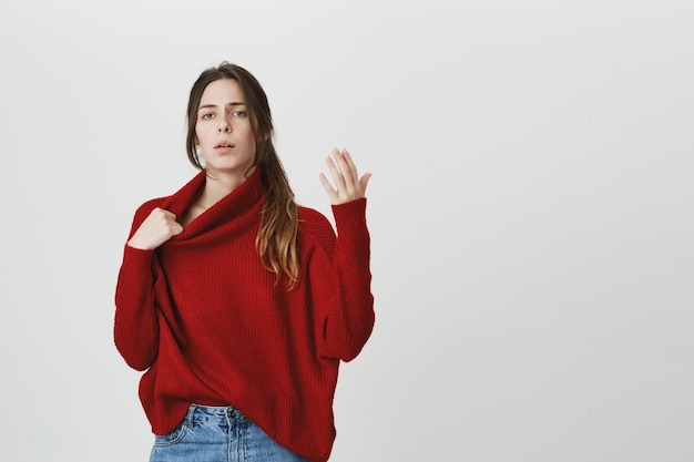 Woman trying cool down, feel hot in sweater