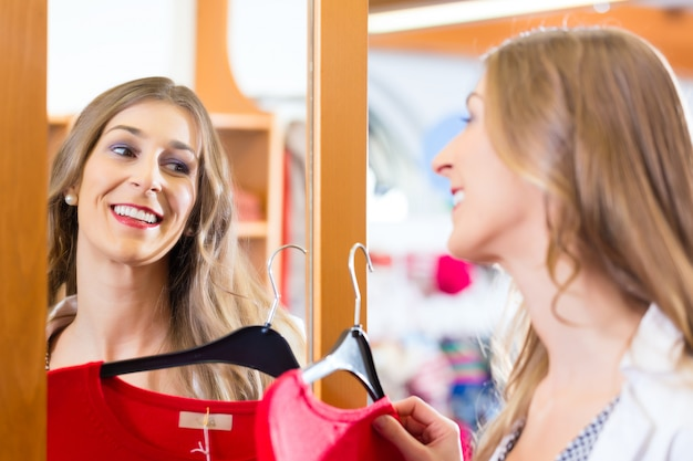 가 게 거울에 패션 옷을 시도하는 여자