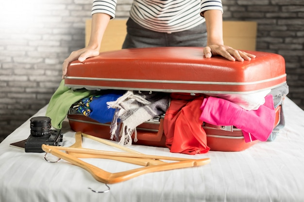 Woman trying to fit all clothing to packing her red suitcase before vacation.