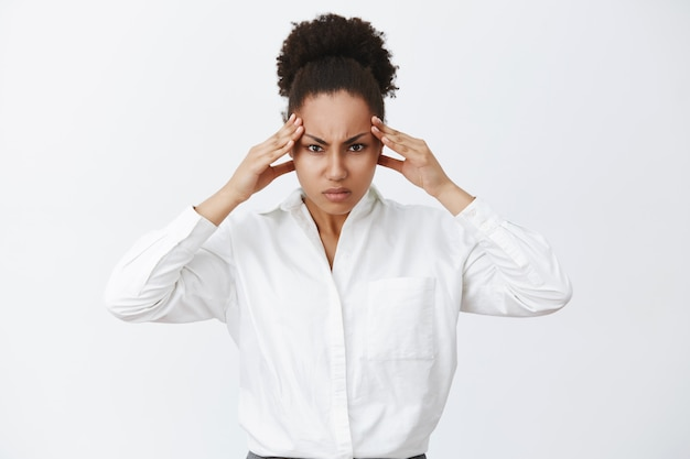 Woman trying focus, searching solutions in brain, being great strategist. portrait of intense businesswoman trying concentrate, frowning, holding hands on temples, thinking hard to find solution