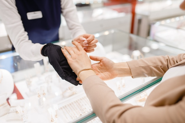 Woman trying on gold bracelet in jewelry store