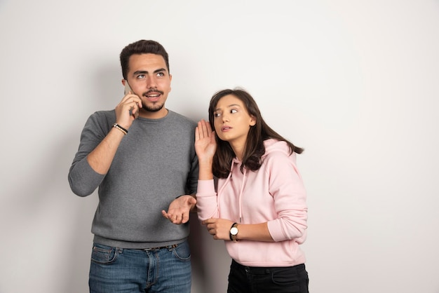 Woman trying to listen what boyfriend talking in telephone.