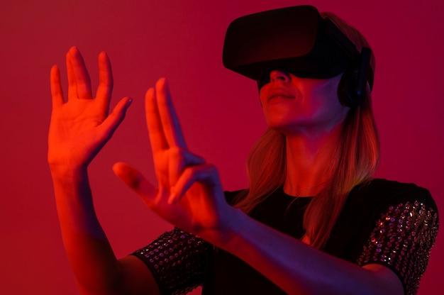 Женщина пробует новое устройство в красном свете