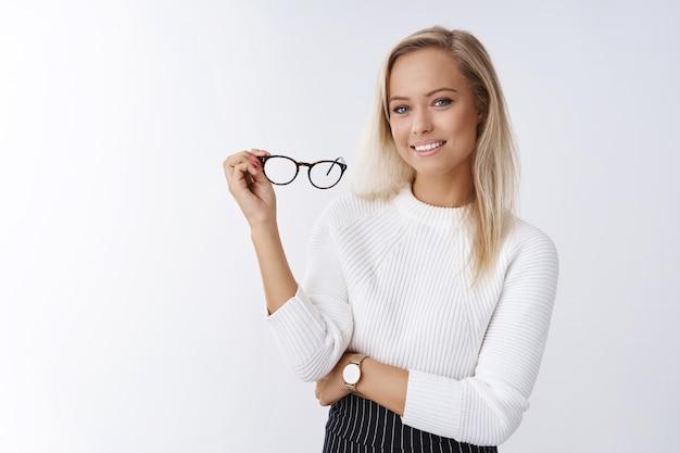 Женщина пробует новые очки в магазине, выбирая правильную оправу, подходящую к стилю, позирующему на белом фоне, уверенная и довольная, улыбающаяся, довольная, держащая очки в руке, чувствуя себя уверенной и успешной.