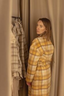 여자 옷가게의 피팅 룸에서 코트를 입으려고