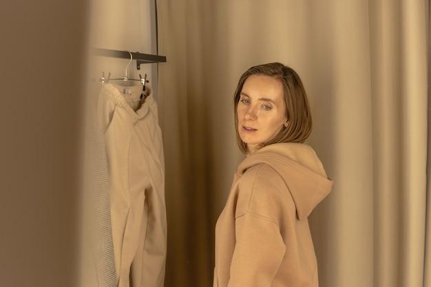 옷가게의 피팅 룸에서 캐주얼 한 벌을 시도하는 여자
