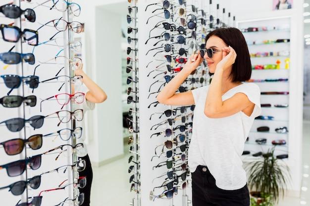 Женщина примеряет солнцезащитные очки в магазине
