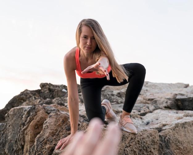 Donna che cerca di raggiungere una mano durante l'arrampicata