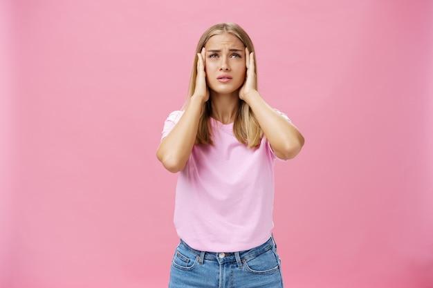 Женщина пытается вспомнить важное число, касаясь висков руками, озабоченными и сосредоточенными, и испытывает проблемы с запоминанием информации, стоя напряженно