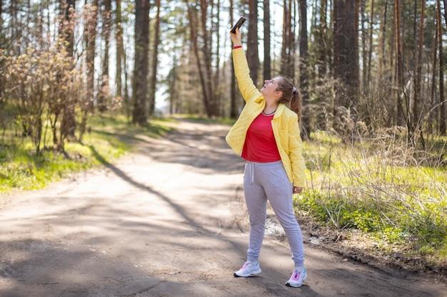 Женщина пытается поймать телефонную сеть труднодоступных районов в лесу g сотовой связи