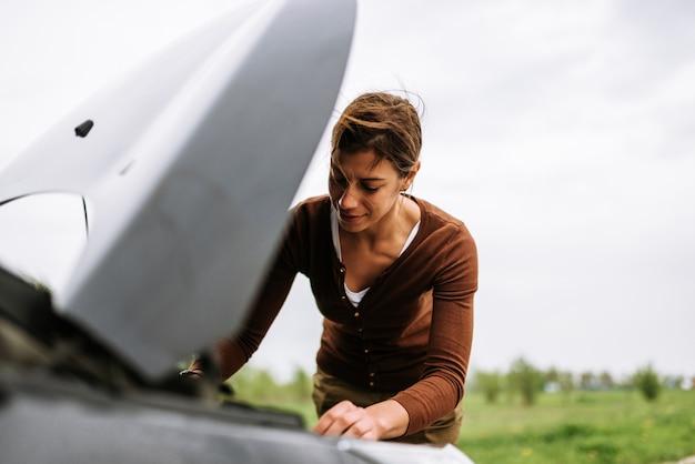 도로, 깨진 후드에 깨진 자동차를 해결하려고하는 여자.