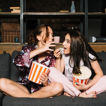 Woman trying to grab popcorn from her friend's hand