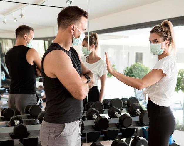 체육관에서 남자를 하이 파이브하려고하는 여자