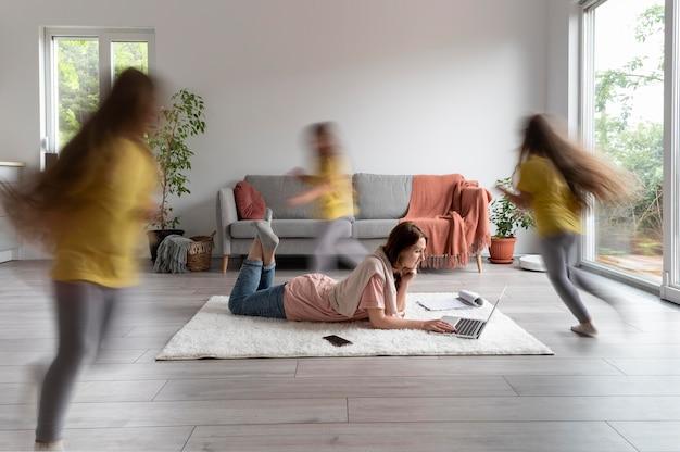 Женщина пытается работать на ноутбуке из дома, пока ее дети бегают