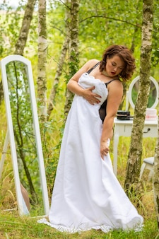 Woman trying on a wedding dress in front of mirror in the forest