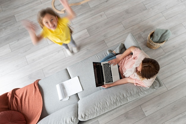 Woman trying to work on laptop from home while her children are running around